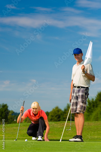 Young sportive couple playing golf on a course