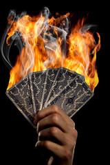 Das Bild zeigt eine Hand, die brennende Karten halt.