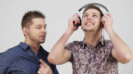 two brothers, listen to music in different-sized headphones