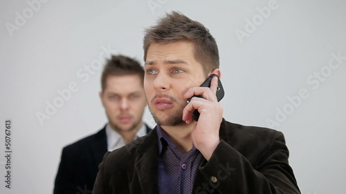 talking on the phone, standing behind a twin brother