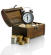Alarm clock with coins in chest isolated on white