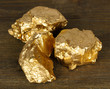 Golden nuggets on wooden background