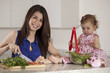 Happy young mother making dinner