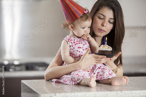 Cute baby girl and her mom blowing the candle of a birthday cake