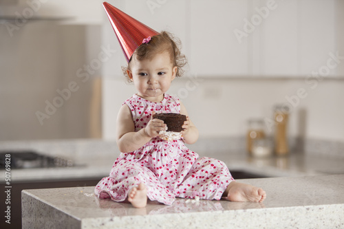 Beautiful baby girl eating cake for her birthday