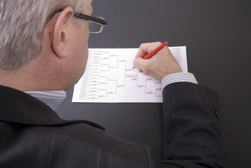 March Madness Businessman Crossing Out Teams on Bracket