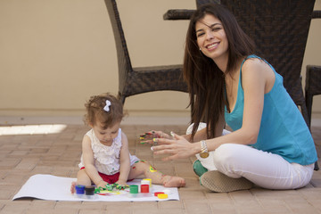 Mom and baby painting outdoors
