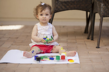Baby girl learning to paint