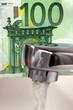 Wasserhahn mit Banknote im Hintergrund