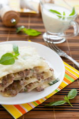 Meat lasagna with grated mozzarella and basil