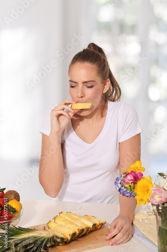 Beautiful young woman eating pineapple