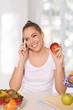 Beautiful young woman eating an apple while talking on the phone