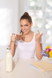 Young beautiful woman drinking a glass of hot drink while making
