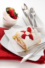 Roll sponge cake with whipped cream and strawberries