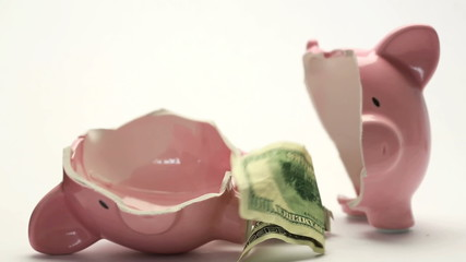 Piggy bank splitting in two halves with cash inside