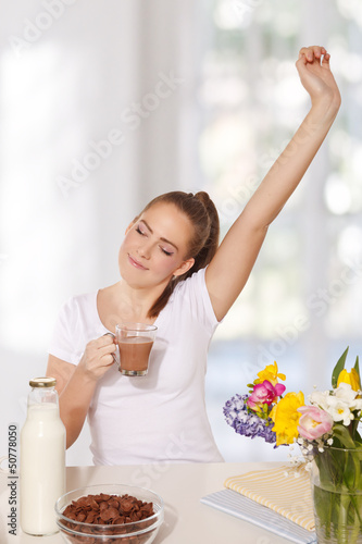 Beautiful young woman streching herself while holding a glass of