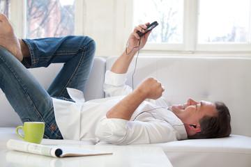 Mann auf dem Sofa liegend mit Smartphone