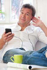 Mann hört auf der Couch Musik