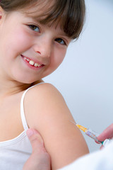 nurce giving vaccination injection to little girl patient