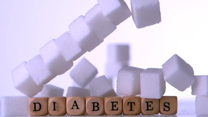 Wall of sugar cubes falling over dice spelling out diabetes