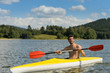 Sporty man in kayak with oar summer