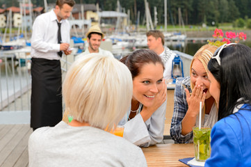 Gossiping women sitting at harbor bar