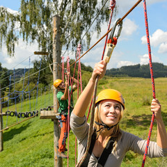 People with ropes in adventure park