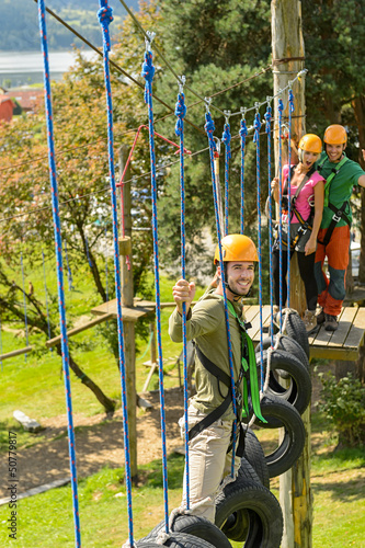 Smiling man climbing in adventure park