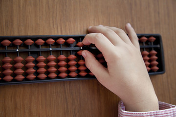 Child´s hand doing arithmetics with a Japanese abacus
