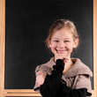 Smiling little Girl in front of schoolboard