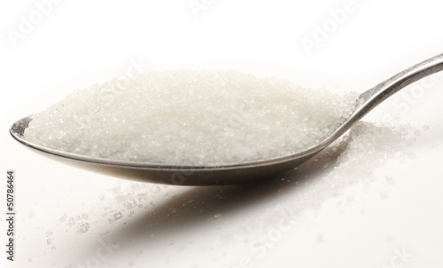Sugar in spoon on white background