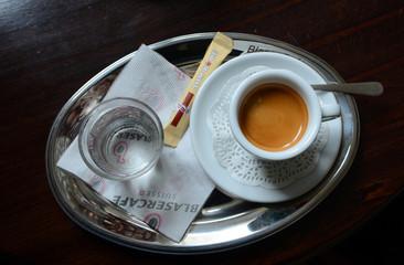 Чашка кофе экспрессо и стакан воды на подносе
