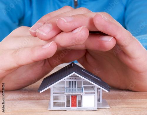Haus mit schützenden Händen darüber
