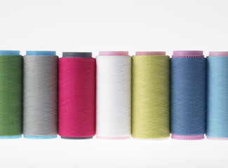 Colors, colorful spools of thread on a white background