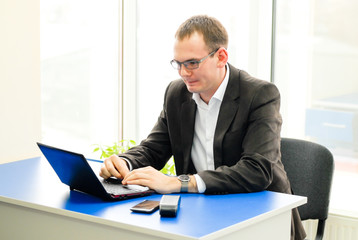 Happy businessman using laptop in office