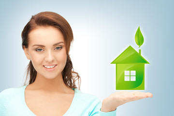 woman holding green house in her hands
