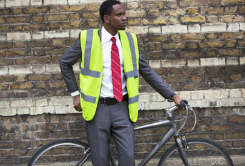 Portrait of African American businessman in safety vest with Bicycle