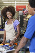 Close-up portrait of an African American female store clerk standing at checkout counter scanning item serving male customer