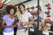 African American woman buying tool at hardware store