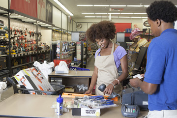 Portrait of an African American female store clerk standing at checkout counter scanning item serving male customer