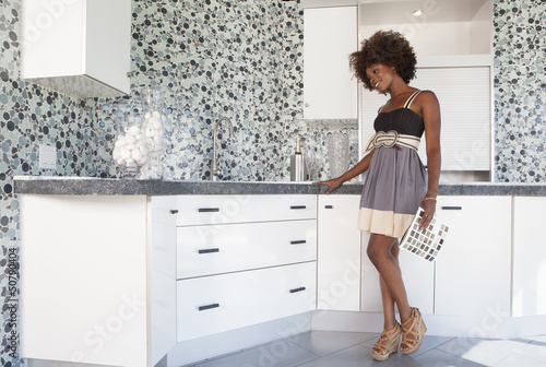 Young African American girl in new furnished Kitchen choosing materials