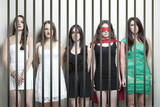 Woman in superhero costume with female friends standing behinds prison bars