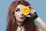 Funky young woman covering eye with sliced orange over blue background