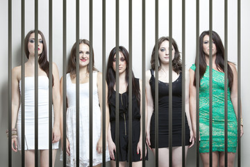 Portrait of five young women standing side by side behinds prison bars