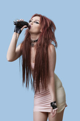 Portrait of funky young woman with bottle of drink over blue background