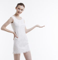 Portrait of young woman in dress with hand on hip over white background
