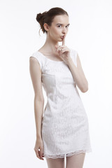 Young woman in dress gesturing to be quiet over white background