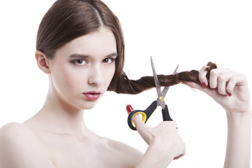 Portrait of beautiful young woman with scissors cutting her hair over white background