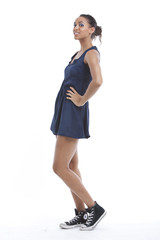 Portrait of young woman wearing mini dress and sneakers against white background