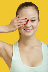 Portrait of a beautiful young woman covering eye over yellow background